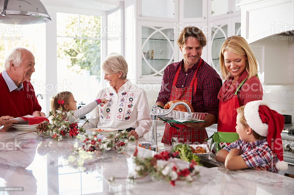 Extended Family Group Preparing Christmas Meal In Kitchen stock photo