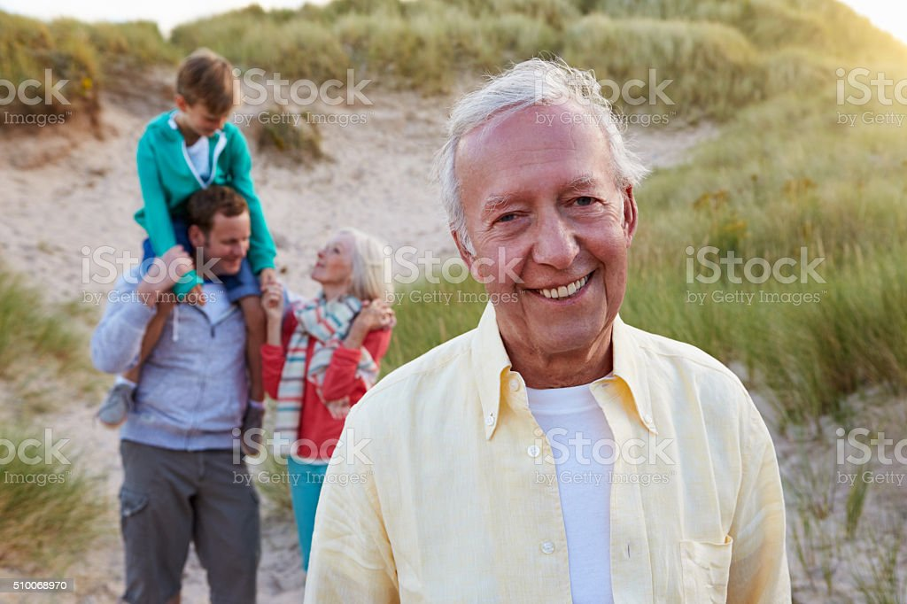 Extended Family Group Walking By Sand Dunes stock photo