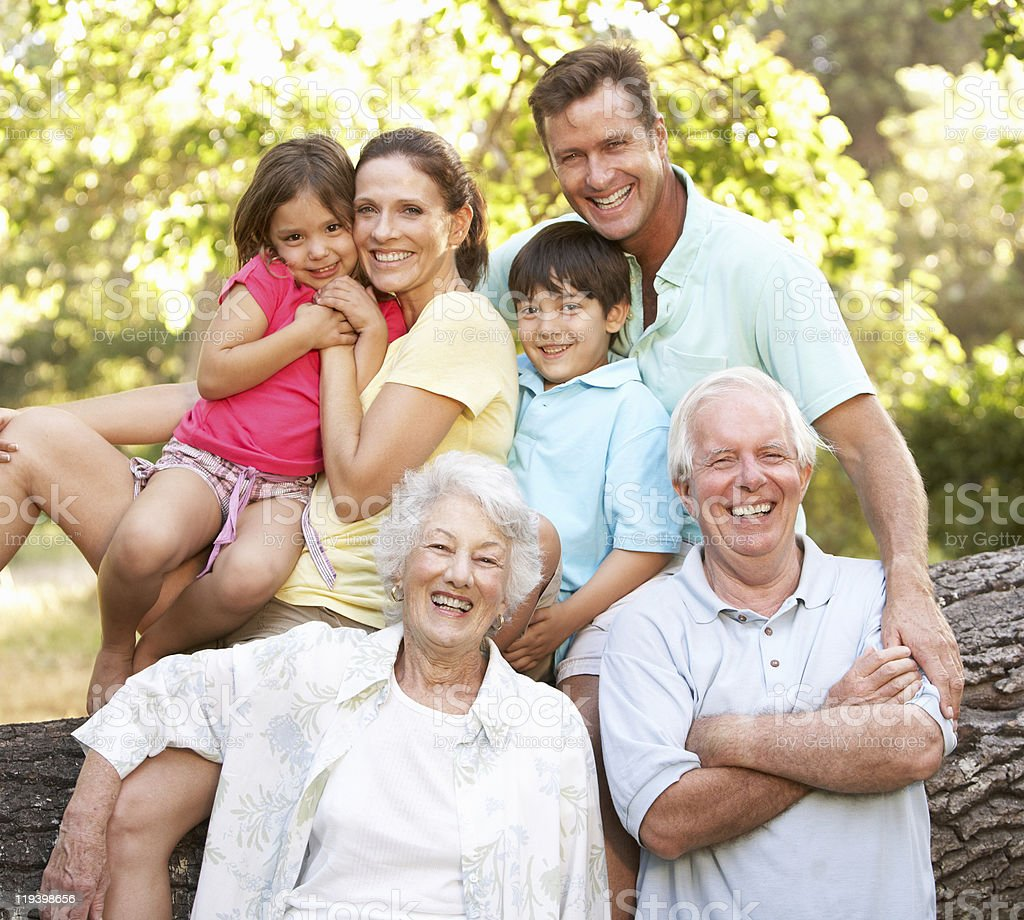 Extended family portrait taken in a park with a tree log royalty-free stock photo