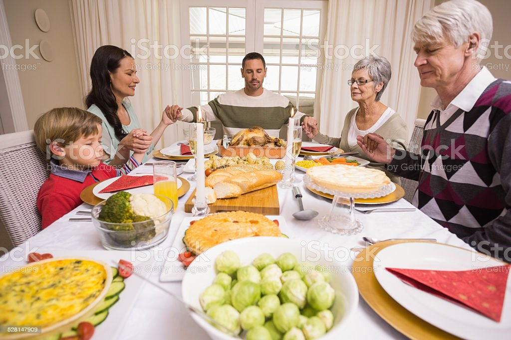 Extended family saying grace before christmas dinner stock photo