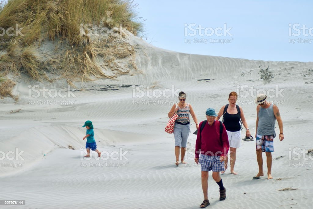 Extended Family walking on Sand Dunes at the Beach. stock photo