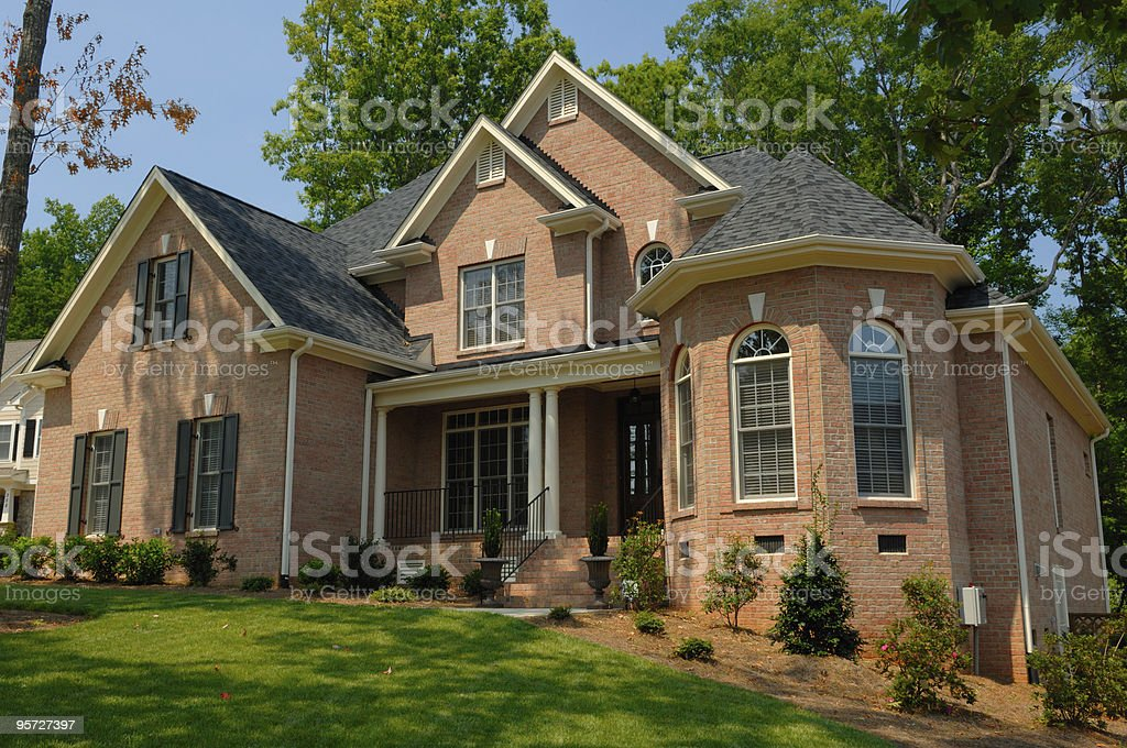 Exterior of a brick executive home with green lawn royalty-free stock photo