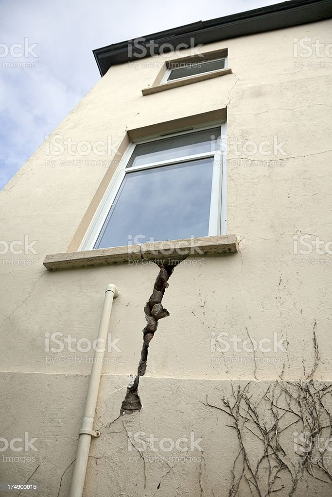 Exterior of a building with crack on wall by the window stock photo