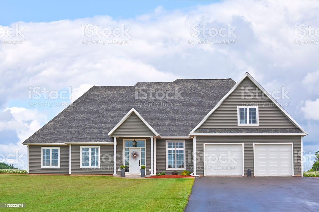 Exterior of a gray country home with a manicured lawn stock photo
