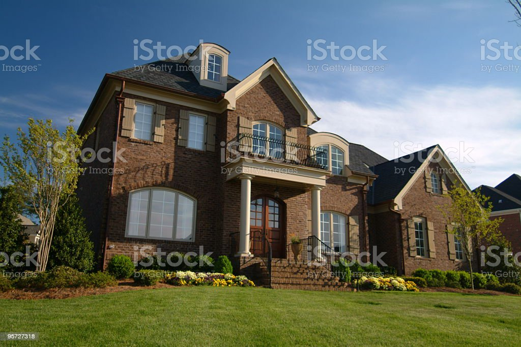 Exterior of a large home made of brown brick with lawn stock photo