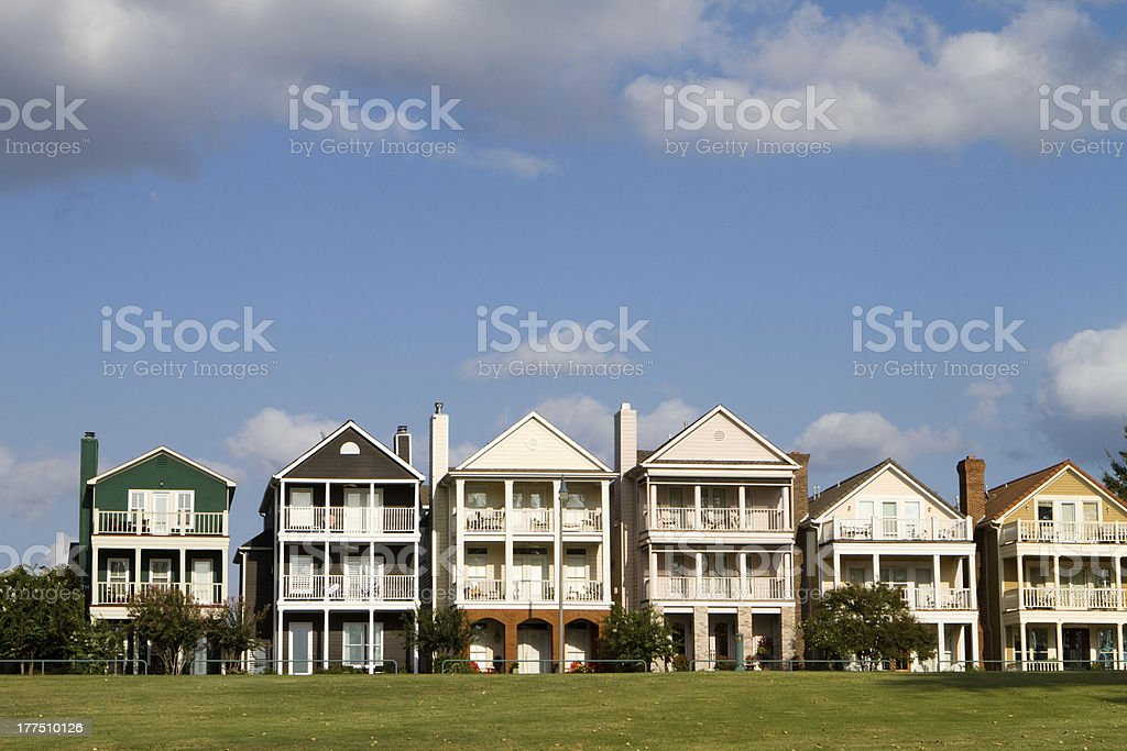 Exterior of a row of upscale townhouses with green grass stock photo