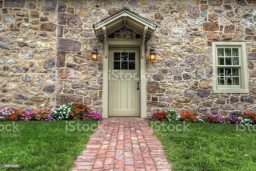 Exterior of a wooden door in a stone facade with brick walk stock photo