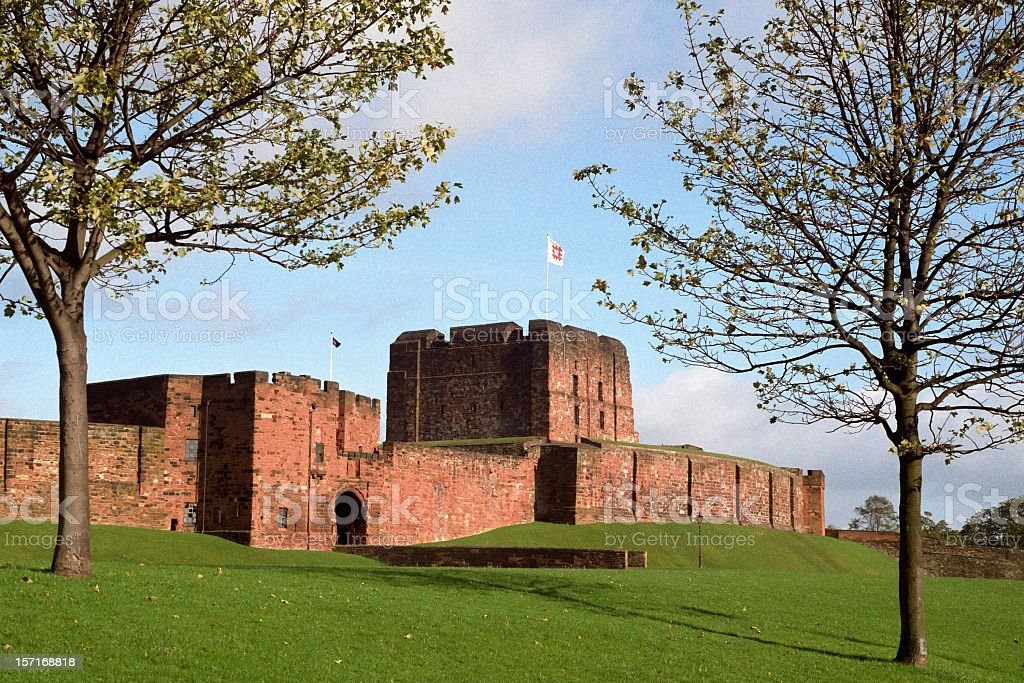 Exterior view of Carlisle Castle with green grass and sky stock photo