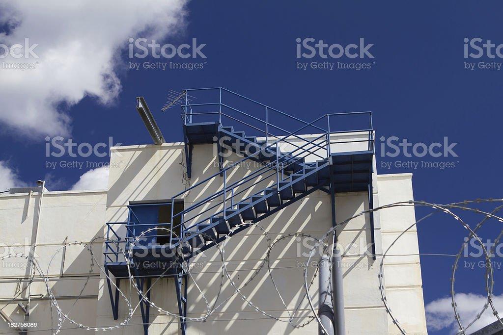 External ladder (fire escape) on a wall aginst blue sky stock photo