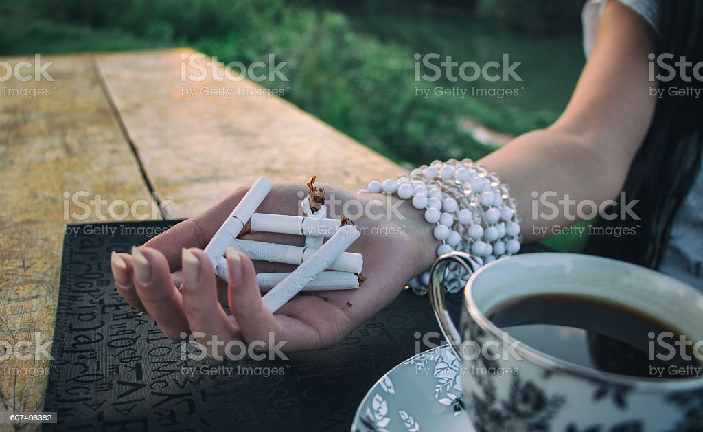 extinguish cigarettes. A young girl breaks a cigarettes stock photo