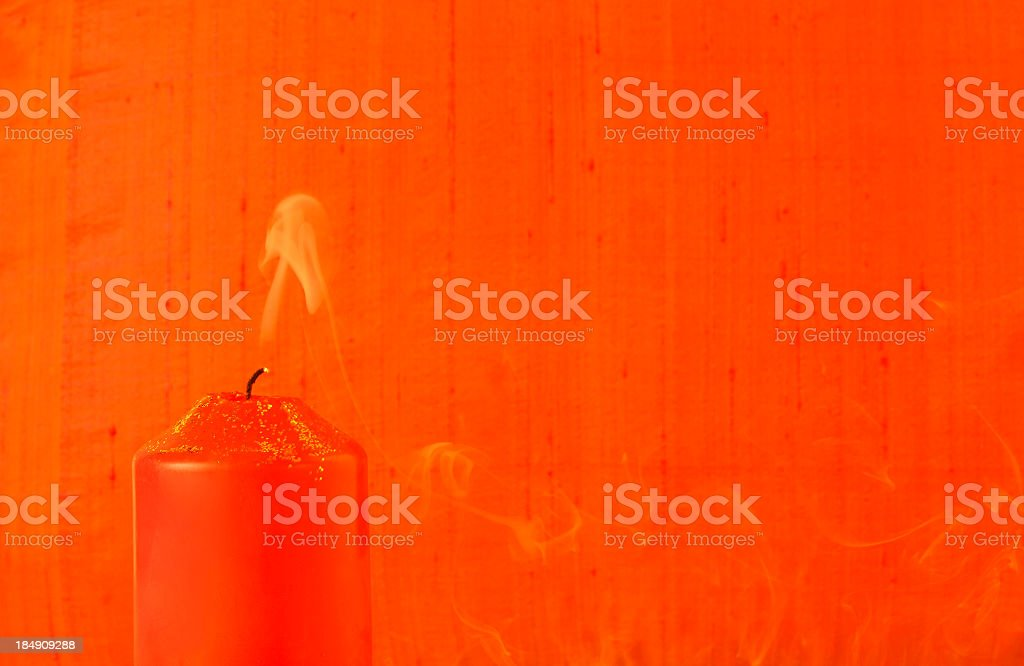 Extinguished light, red candle, golden glitter, smoke, textile background stock photo
