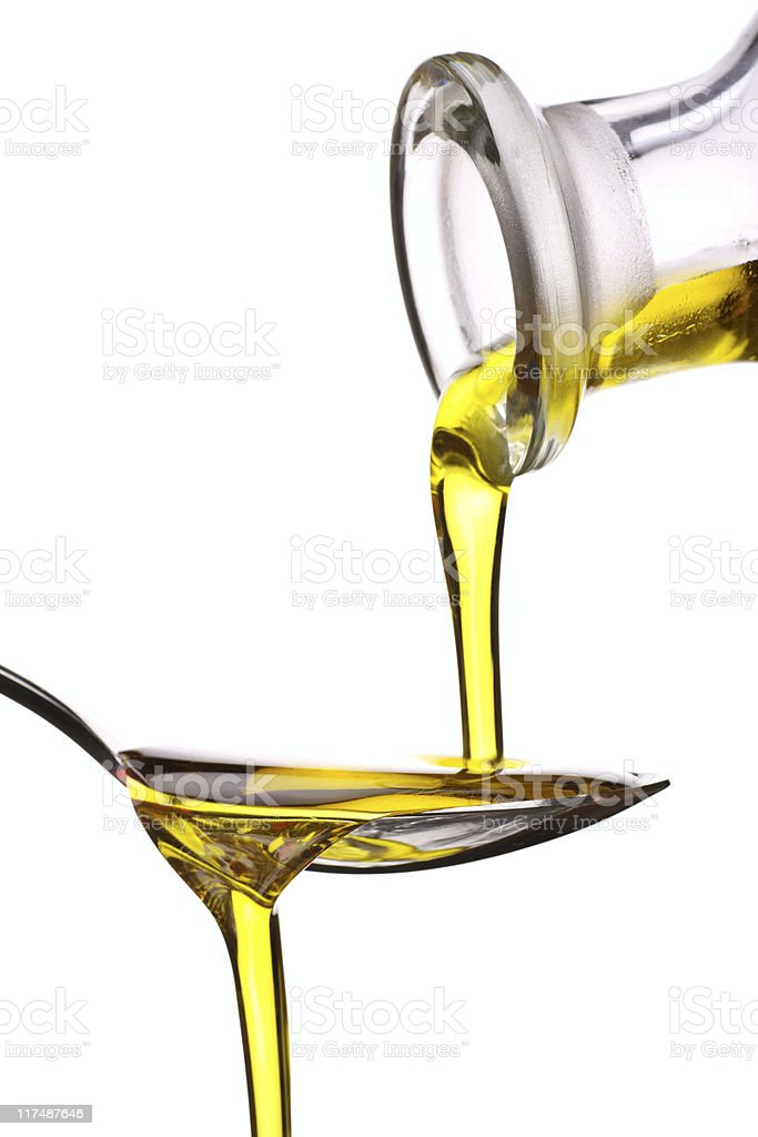 Extra Virgin oil being poured on a spoon royalty-free stock photo