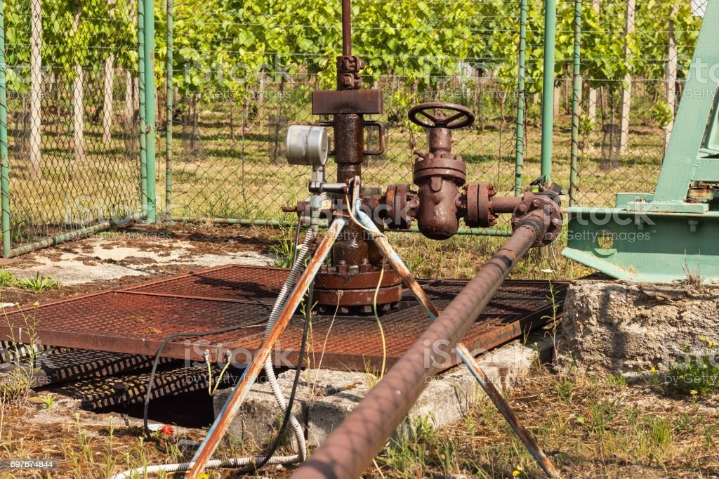 Extraction of good quality oil. Oil well pumpjack on vineyard stock photo