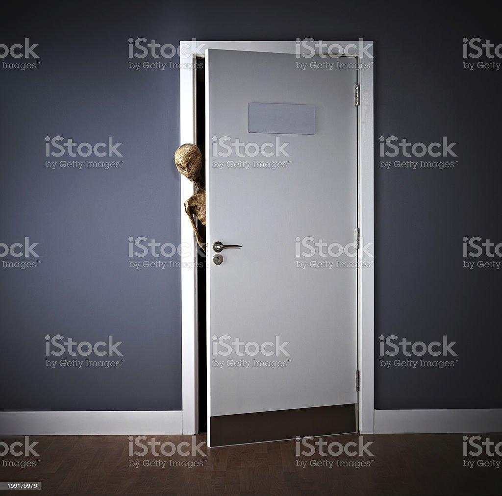 Extraterrestrial peering around an open door royalty-free stock photo
