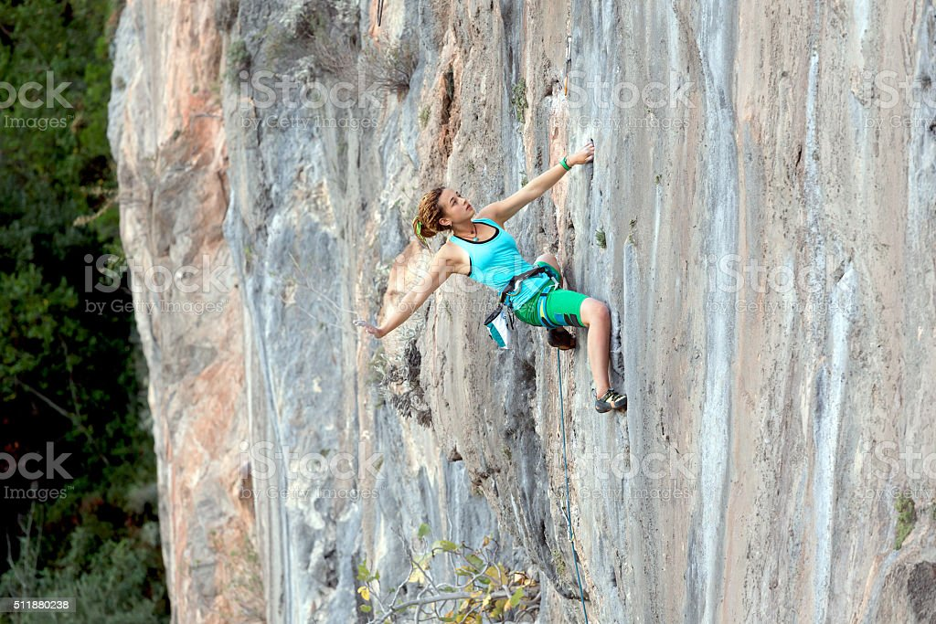 Extreme Athlete on rocky Wall makes relaxed elegant Move stock photo