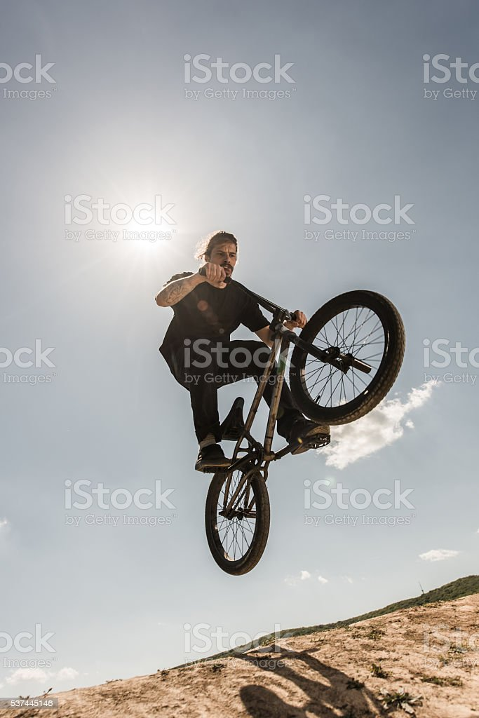 Extreme bicycle rider jumping against the blue sky. stock photo