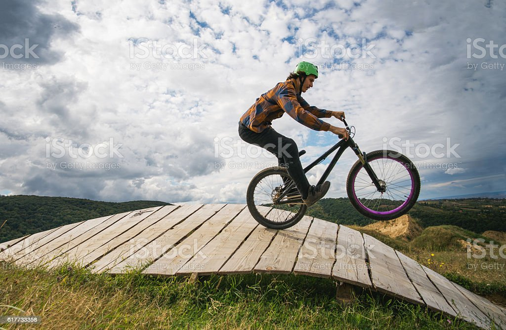 Extreme bicycle rider performing wheelie over wooden ramp. stock photo