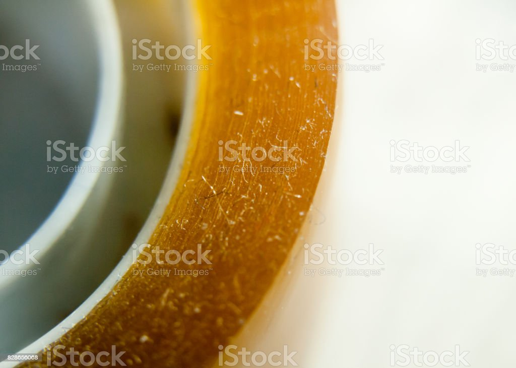 extreme close up of yellow sticker tape cellophane on white background stock photo