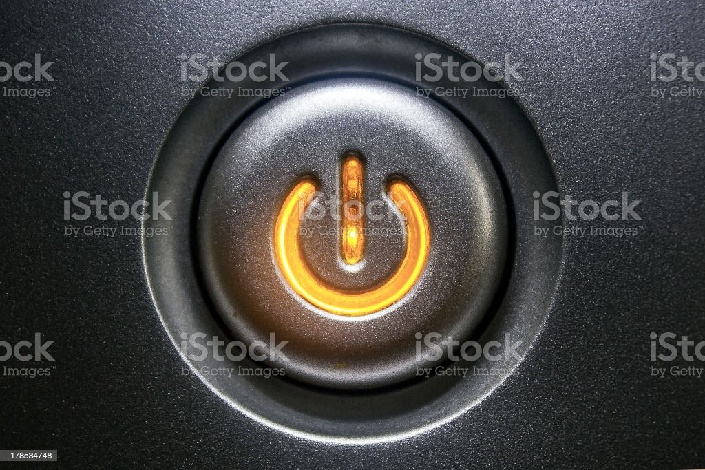 Extreme close-up of a black standby button glowing orange stock photo