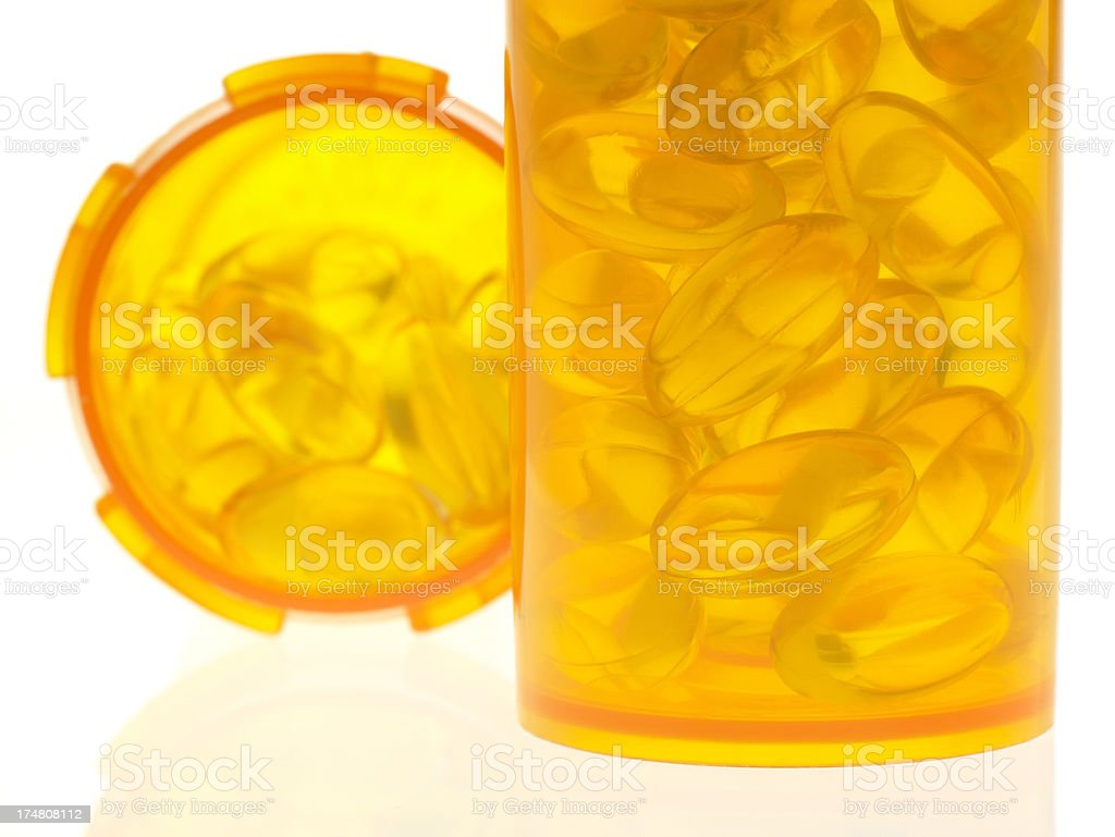 Extreme close-up of capsules in bottles on bright white background royalty-free stock photo