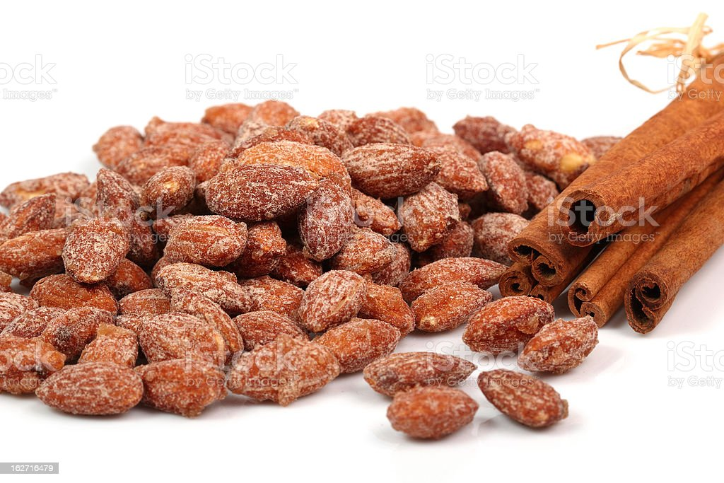 Extreme close-up of sugared cinnamon almonds on white desk stock photo