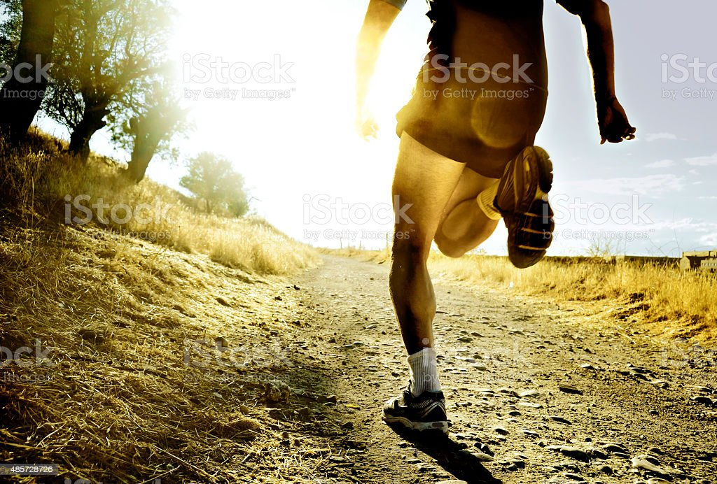 extreme cross country sport man running at sunset harsh light stock photo