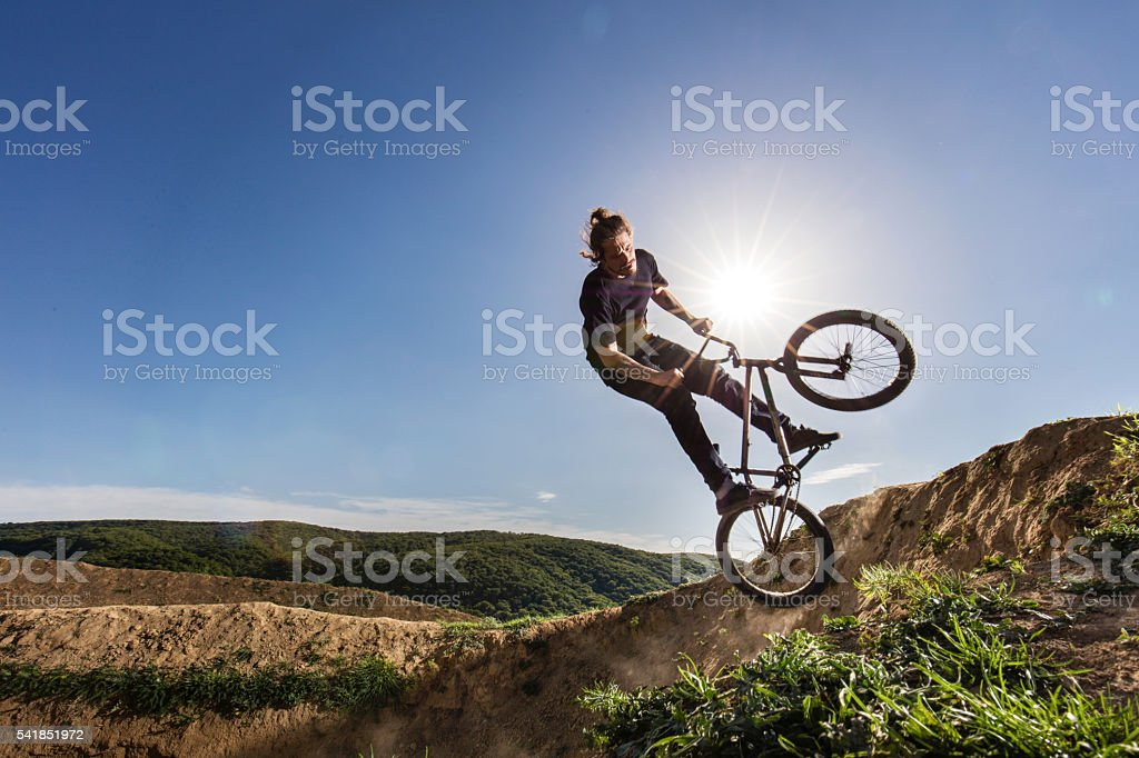 Extreme cyclist practicing on dirt road against the sky. stock photo