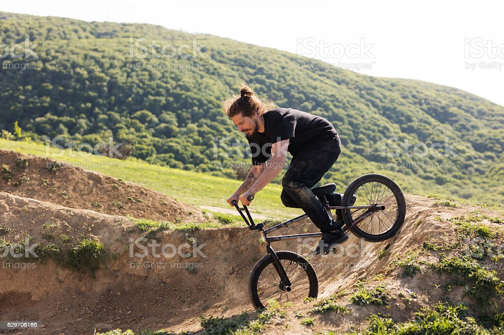 Extreme cyclist riding down the hill on dirt road. stock photo