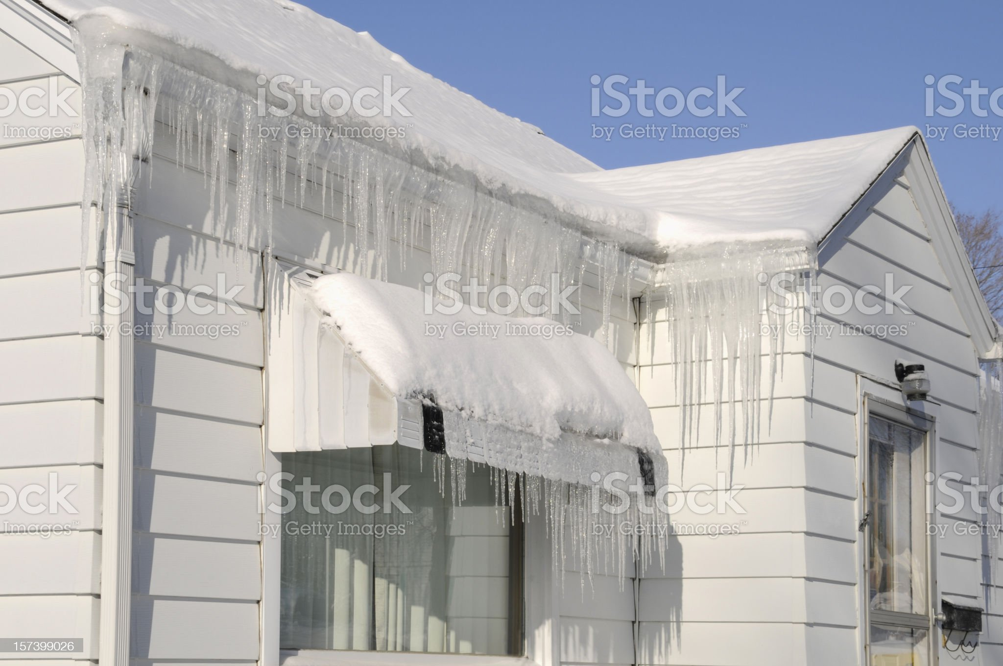 Extreme Icicles, Snow, House Roof After Winter Blizzard; Weather Damage royalty-free stock photo