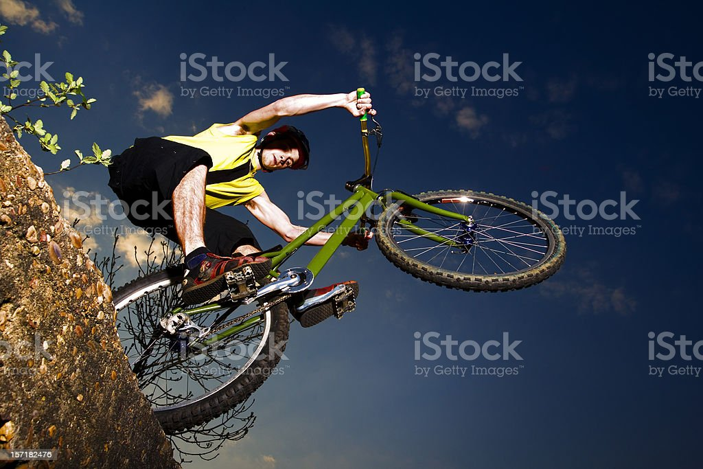 Extreme mountain biker jumping off a rock royalty-free stock photo