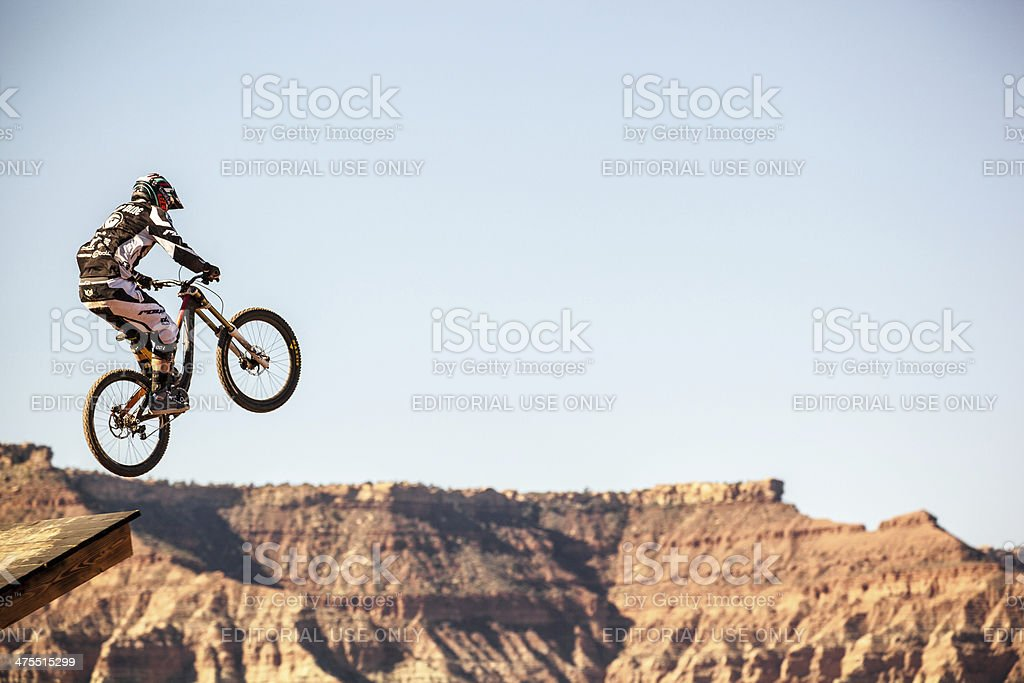 An extreme mountain biker jumps over desert badlands on his mountain...