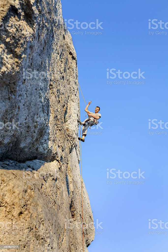 Extreme rock climbing, man on natural wall with blue sky. stock photo