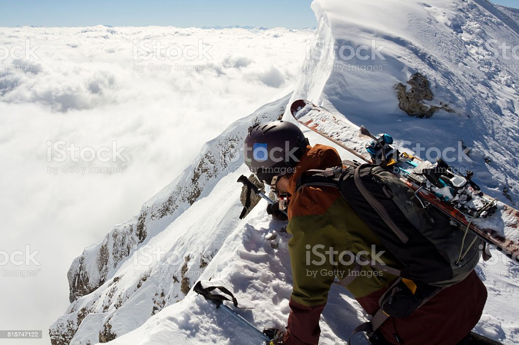 Extreme skier looking down from a cliff edge stock photo