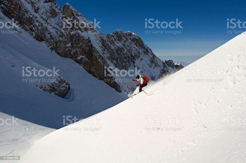 Extreme skier riding down on a snow spine stock photo