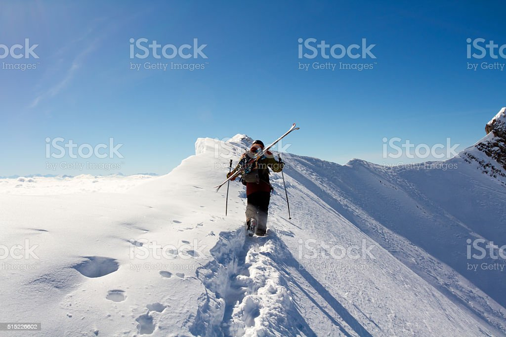 Extreme skier walking on a mountain ridge stock photo