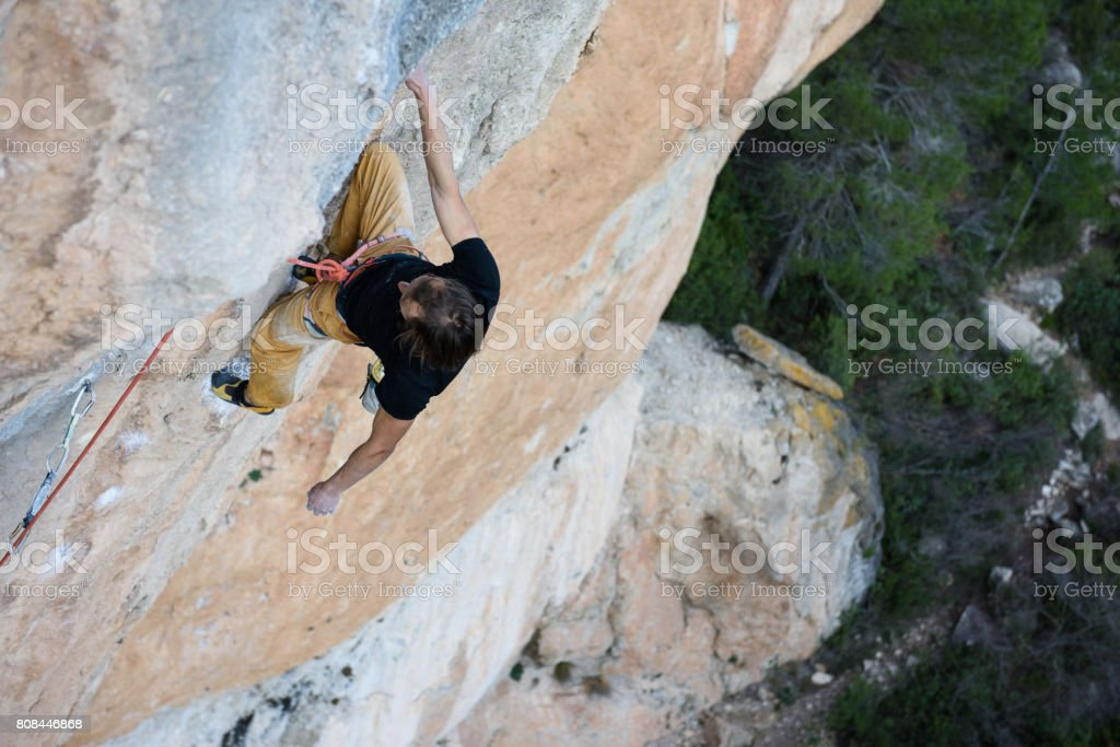 Extreme sport climbing. Rock climber struggle for success. Outdoor lifestyle. A person trying hard to reach sucsess. stock photo