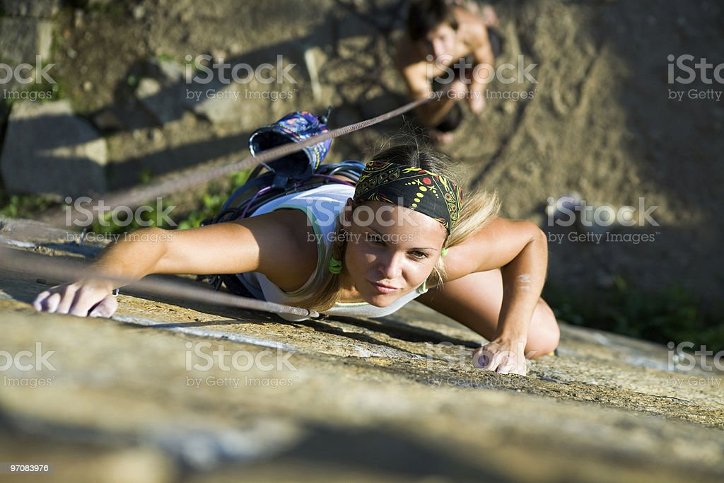 Extreme sport with a woman climbing a vertical wall outdoors stock photo