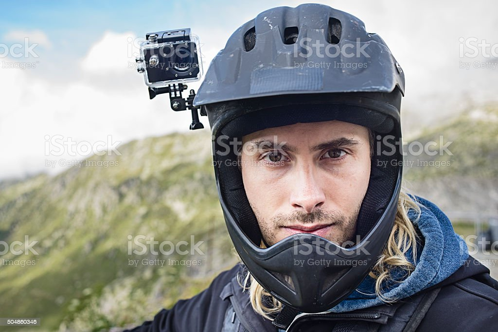 Extreme Sportsman with Action Video Camera in Mountains stock photo