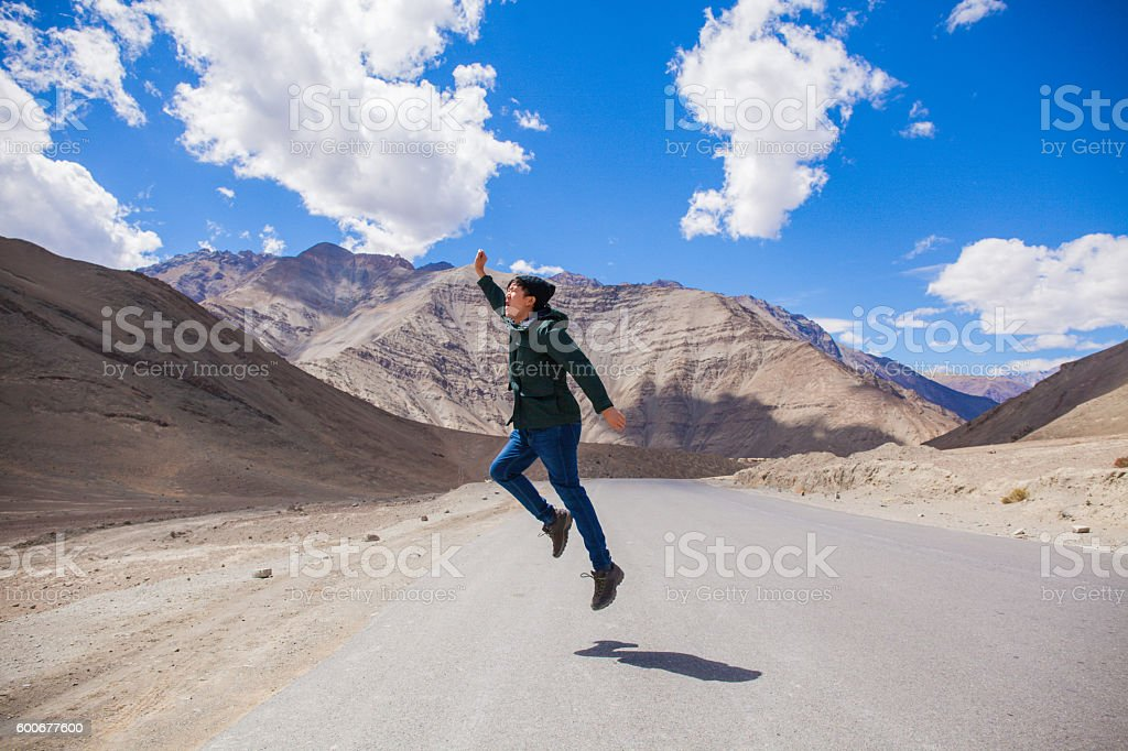 Extremely happy young male tourist jumping on country road stock photo