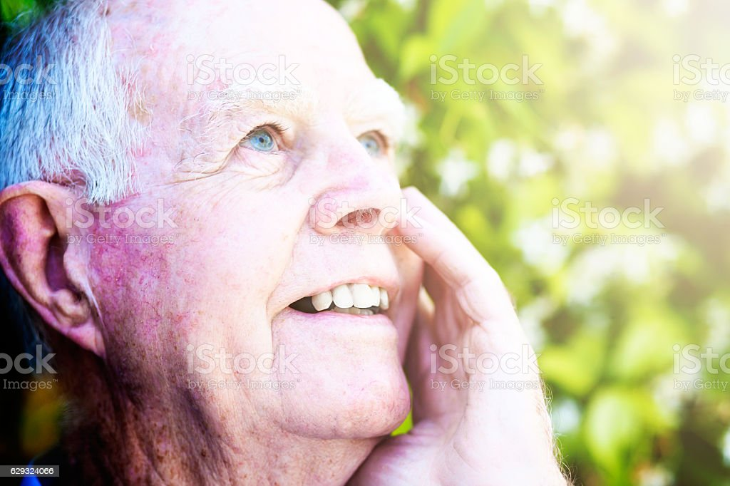 Extremely old man looks up at sky, smiling gently stock photo