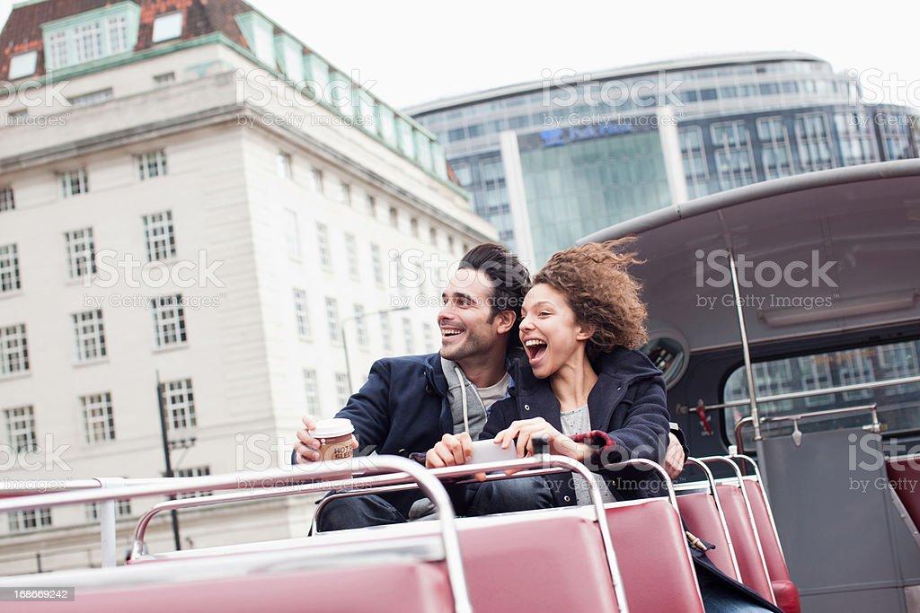 Exuberant couple riding double decker bus in London stock photo