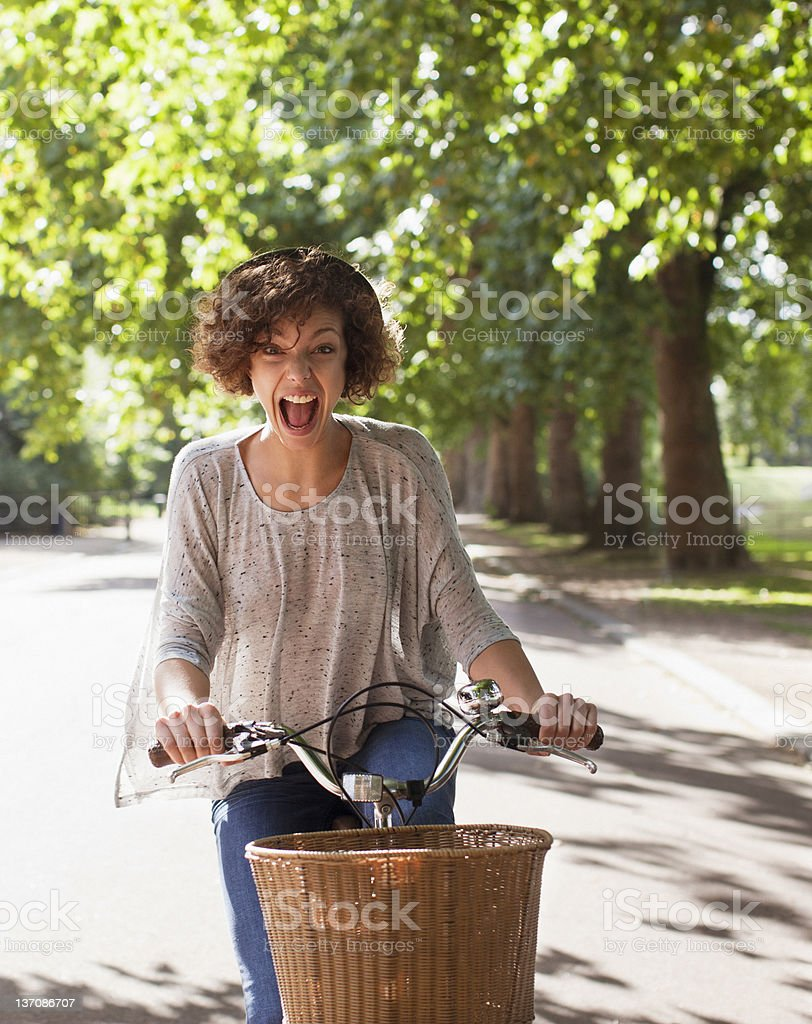 Exuberant woman with mouth open riding bicycle in park stock photo