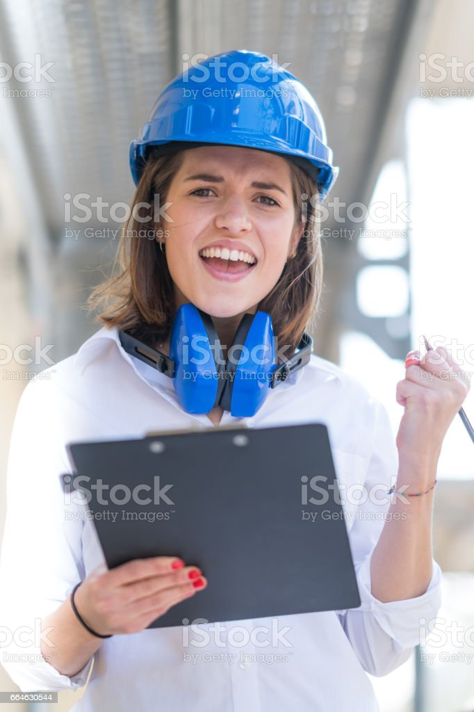 Exulting young beautiful engineer with blue hardhat, protective headphones around her neck and clipboard against scaffolding. Selective focus stock photo