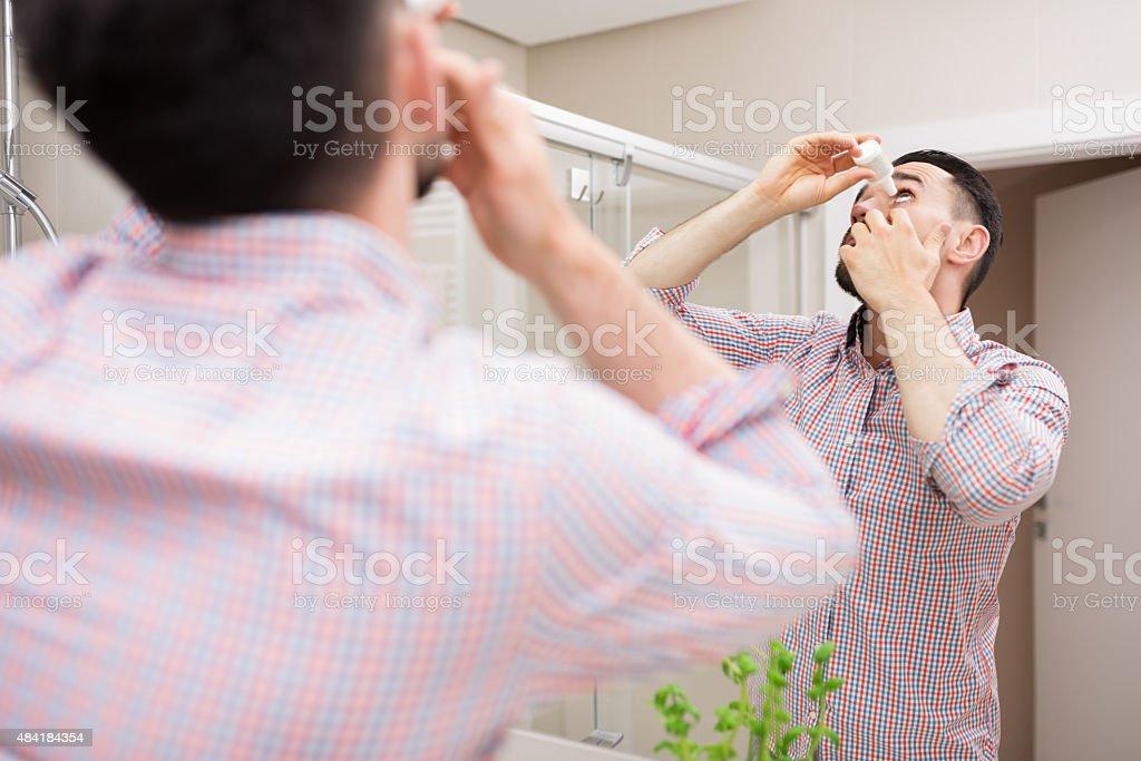 Eye caring with eyedrops stock photo