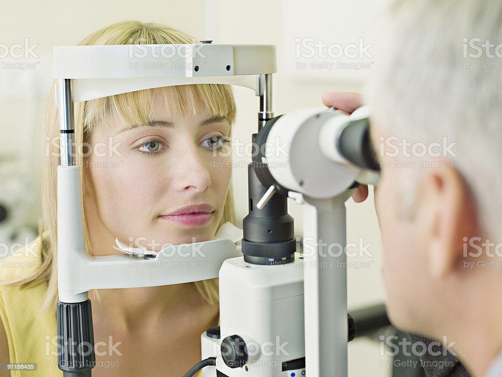 Eye doctor examining womanÕs vision royalty-free stock photo