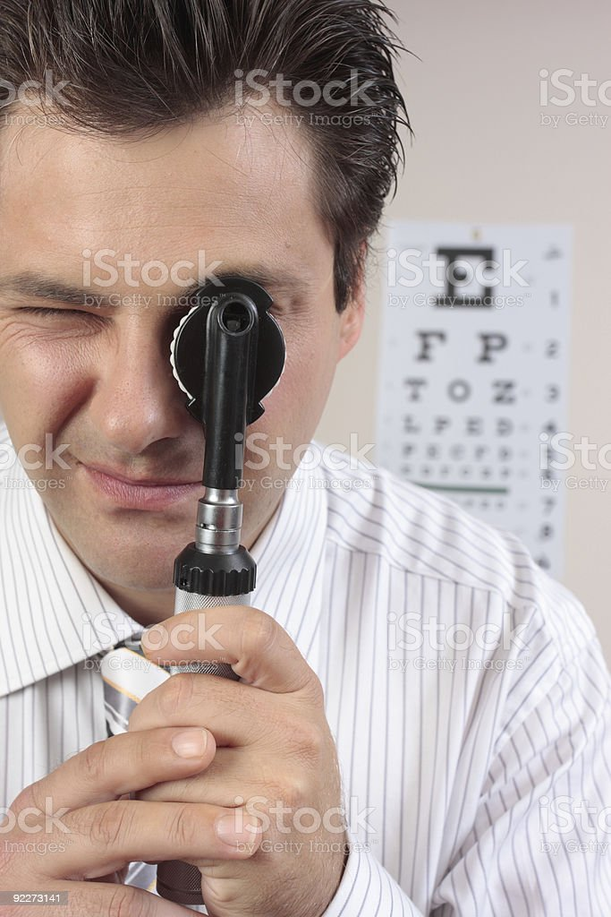 Eye doctor using opthalmoscope stock photo