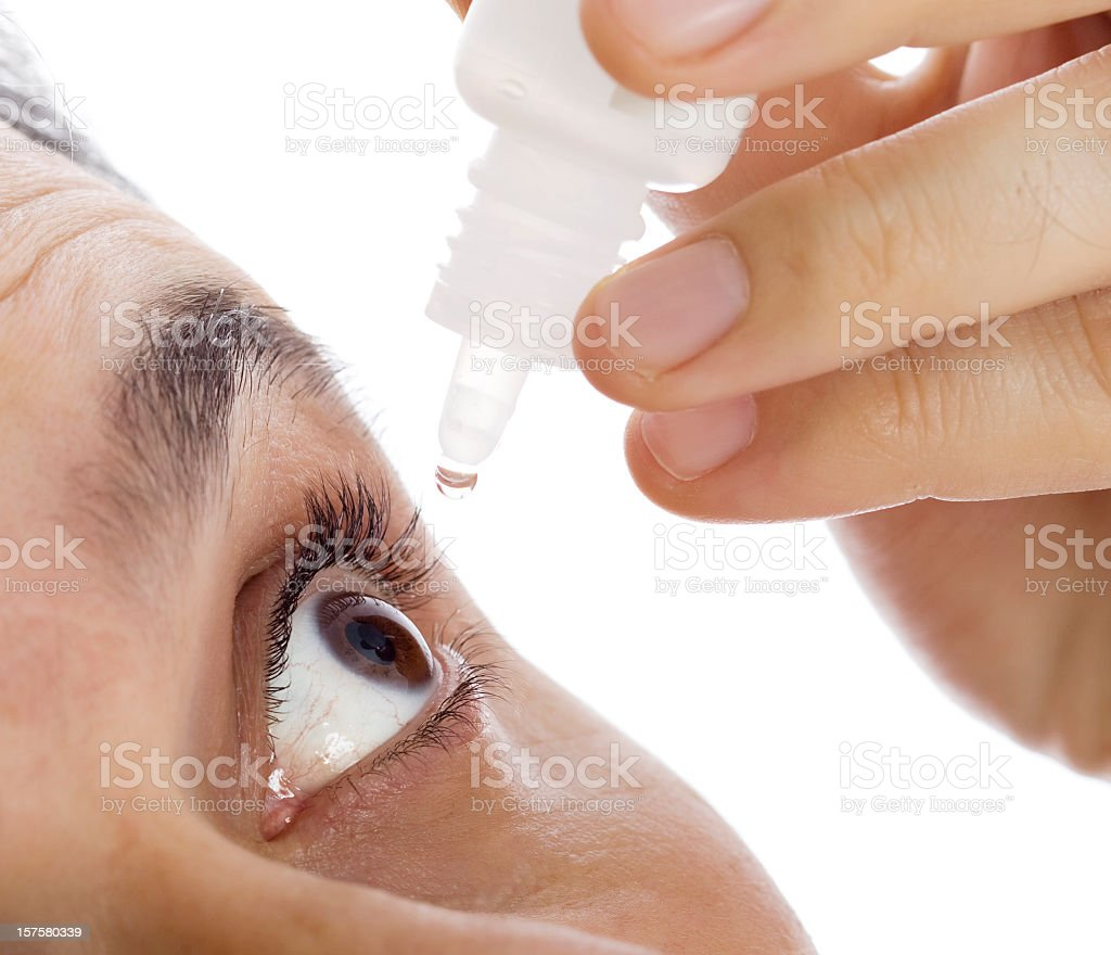 Eye dropper hovering over mans eye stock photo