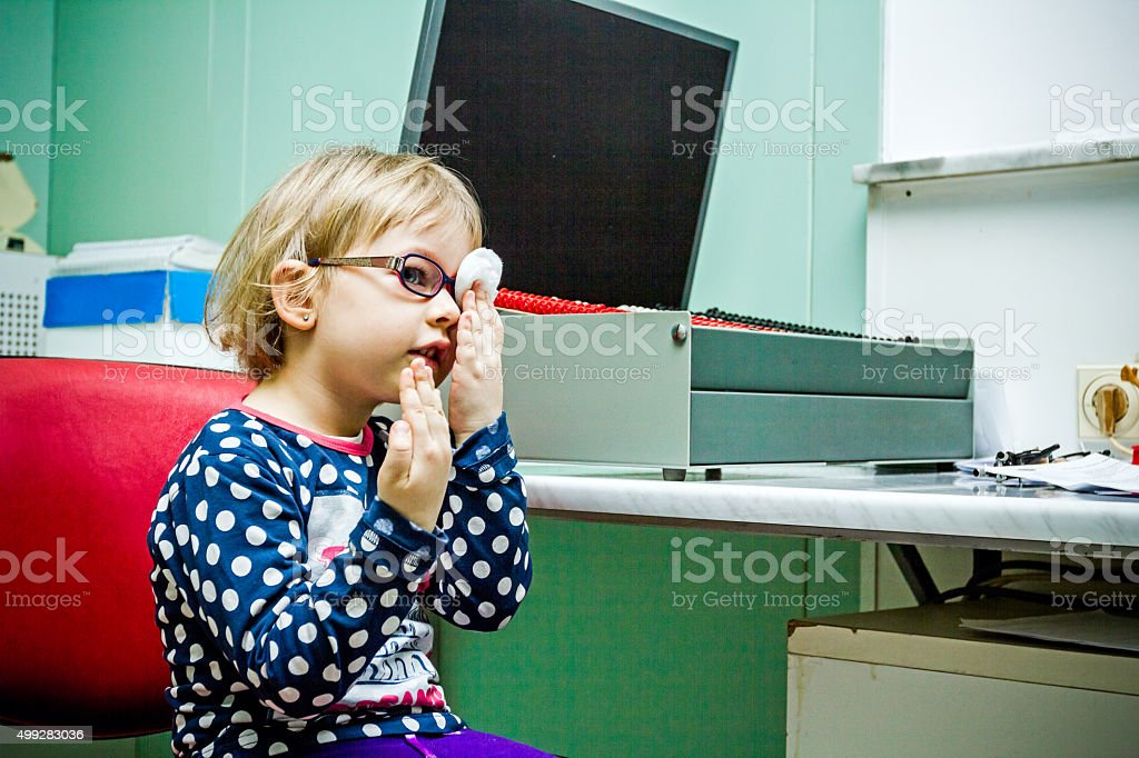 Eye exam, cute little girl is reviewing eyesight. stock photo