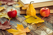 Eye glasses with book and autumn leaves on table