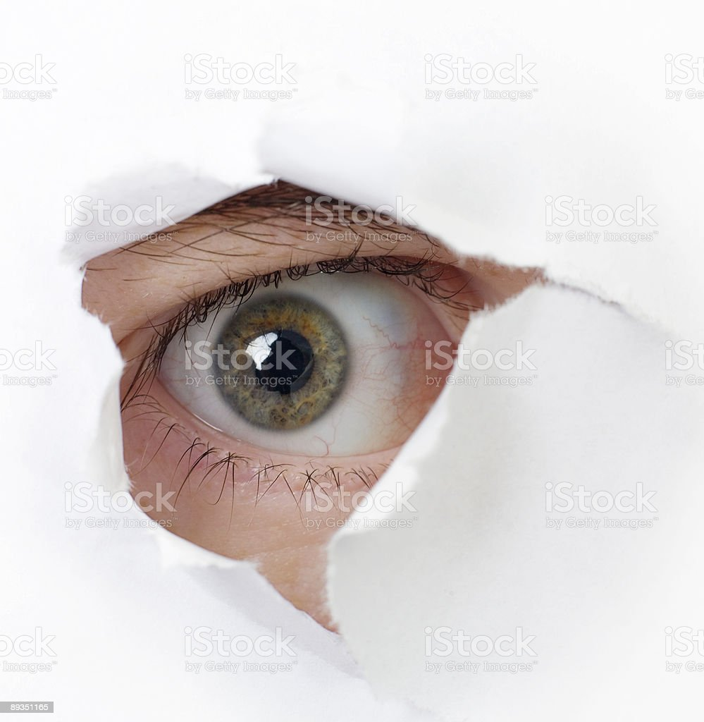 Eye looking through a hole stock photo